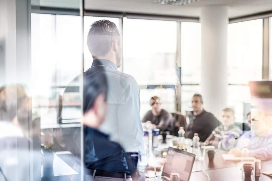 Geschäftsmann hält Präsentation im Besprechungsraum mit großen Fenstern mit voll besetztem Tisch und Laptop hinter Glaswand vor Kollegen mit verschränkten Armen