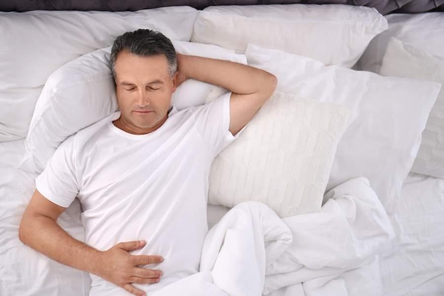 Mann mittleren Alters in weißem T-Shirt hat die Augen geschlossen und liegt auf dem Rücken im Bett mit weißer Bettwäsche mit einer Hand unter dem Kopf, einer Hand auf dem Bauch, Vogelperspektive