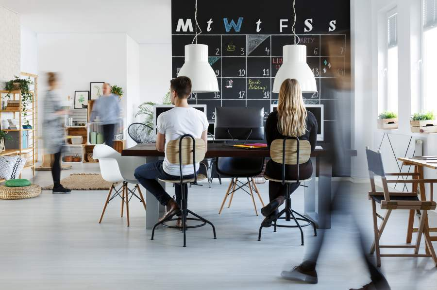 Junge Menschen im Coworking Space mit origineller Einrichtung, zwei Personen sitzen an Büroarbeitsplätzen, drei Personen bewegen sich als verschwommene Umrisse, heller Raum