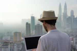 Junger Mann mit Sonnenhut arbeitet als digitaler Nomade auf dem Dach eines Hochhauses in urbaner Umgebung mit Hochhaus-Skyline im Hintergrund, er trägt einen Sonnenhut und weißes Shirt und arbeitet am Laptop, Rückenansicht