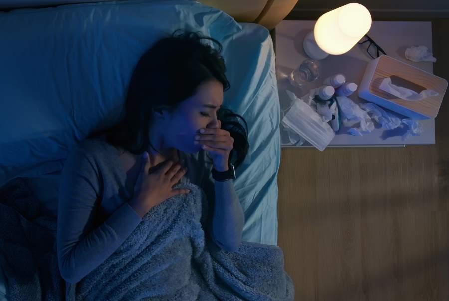 Eine Asiatische Frau liegt in einem halbdunklen Schlafzimmer seitlich unter mehreren blauen Decken in einem Bett und hält sich die Hand hustend vor das Gesicht während rechts neben ihr auf einem Nachtisch eine kleine weiße Nachtischlampe brennt, die neben verschiedenen Medikamentenpackungen und einer Taschentuchbox steht.