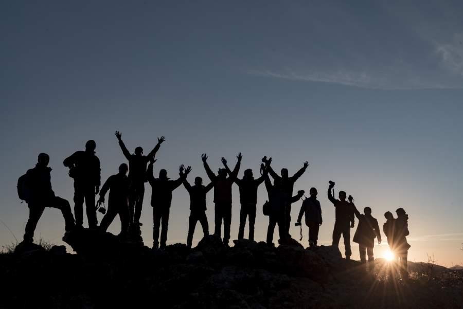 Silhouetten von einer Gruppe von Menschen bei Offsite-Tour mit Rucksäcken vor Sonnenuntergang