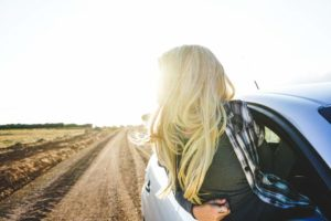 Junge blonde Frau lehnt sich im Sonnenschein aus dem offenen Beifahrerfenster auf einer Landstraße im Sonnenschein