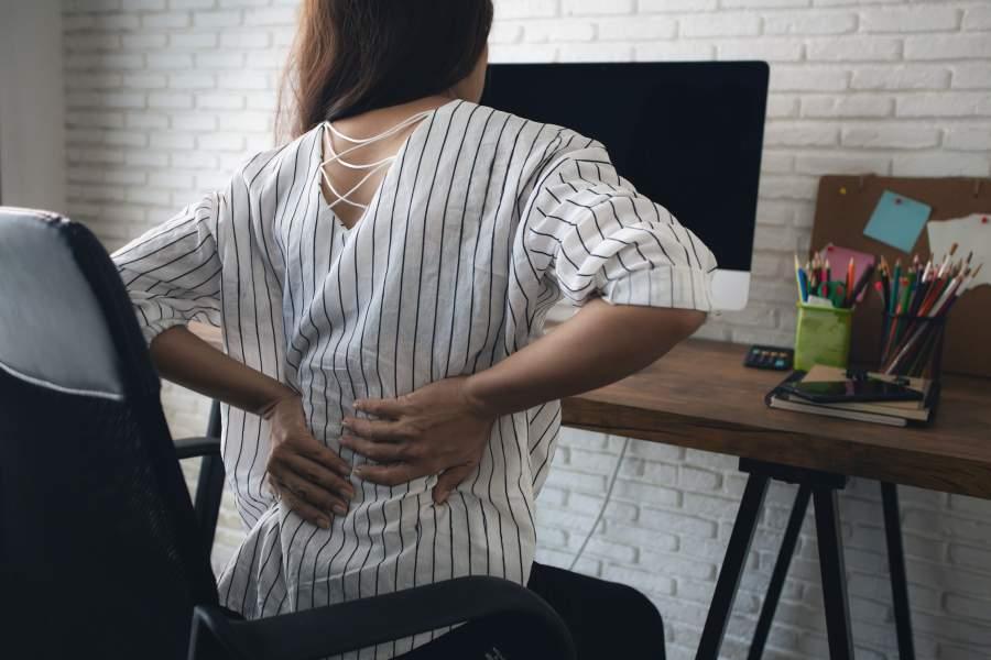 Frau mit gestreifter Bluse sitzt vor ihrem Schreibtisch und hält sich schmerzverzehrt den unteren Rücken.