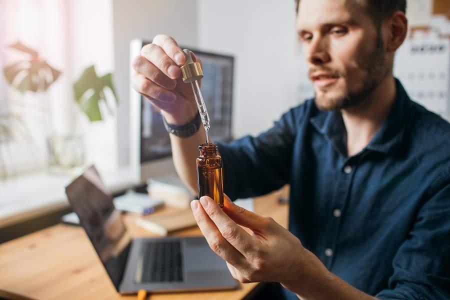 Mann am Schreibtisch mit kleiner CDB-Öl-Flasche und Pipette