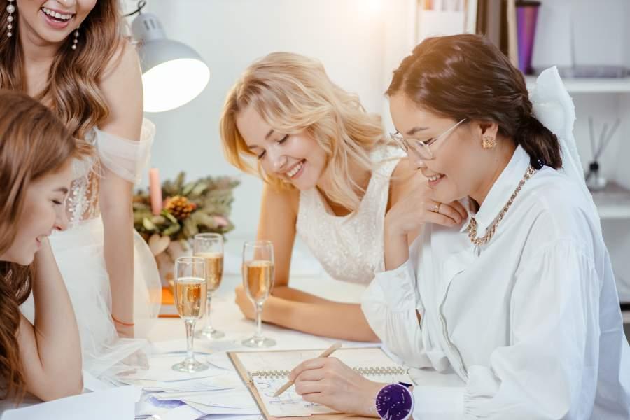 Drei junge, lachende Frauen sitzen mit einer Verkäuferin an einem Tisch auf dem vier Sektgläser stehen und suchen ein Brautkleid aus.