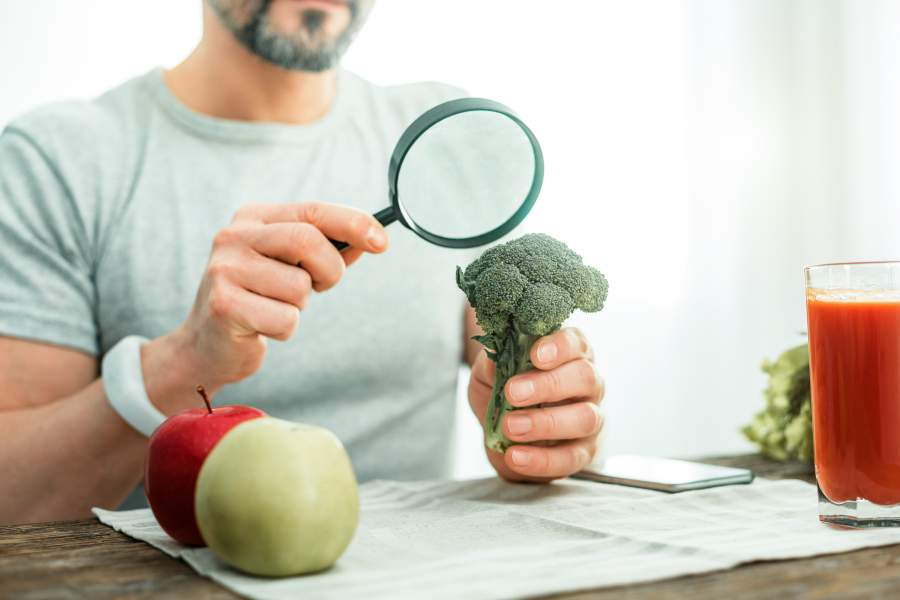 Mann sitzt an Tisch und betrachtet Gemüse und Obst durch eine Lupe, in der Hand ein Brokkoli