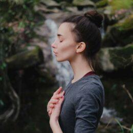 Junge Frau im Profil steht in der Natur und macht eine Atemübung, ein Wasserfall im Hintergrund