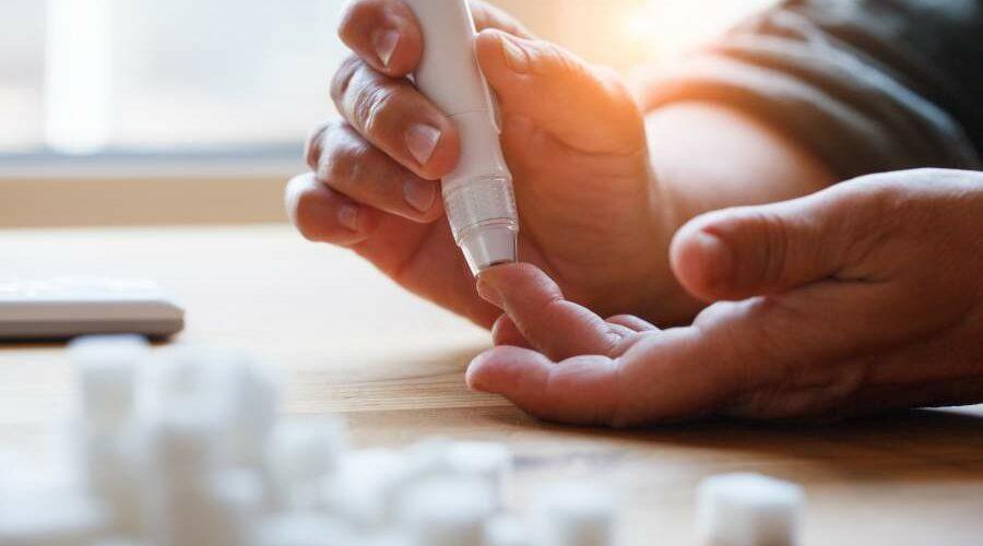 Person sticht mit Blutzuckermessgerät in den Finger um zu messen, im Vordergrund sind verschwommen einige Würfelzucker zu sehen