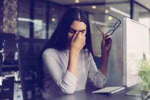 Frau sitzt vor Bildschirm am Schreibtisch und reibt sich die Augen.