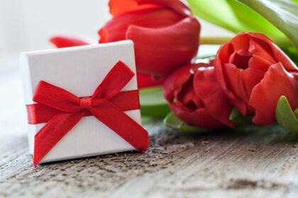Kleine weiße Geschenkbox mit roter Schleife neben roten Rosen auf einem Holztisch