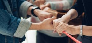 Die Hände mehrerer Personen halten ein rotes Seil gespannt
