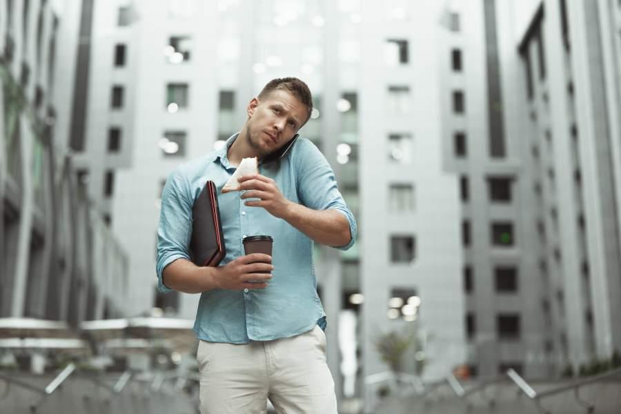 Junger, sportlich gebauter Mann in Hemd und heller Hose vor Bürogebäude wirkt gestresst, telefoniert unterwegs und hält ein angebissenes Sandwich, einen Coffee-to-go-Becher und eine Mappe in der Hand