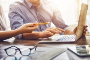 Zwei Personen in einer Besprechung mit Laptop, Stift und Unterlagen