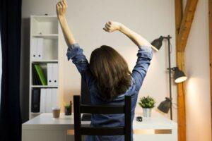 Rückensicht einer Frau, die sich streckt und im Homeoffice mit künstlichen Lichtquellen arbeitet