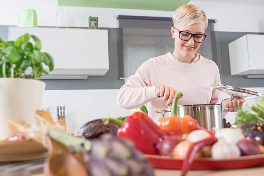 Junge Frau rührt in einem großen Kochtopf in einer hellen Küche um, im Vordergrund Chilischoten, Knoblauch, Paprika, Zwiebeln, ein Topf frischer Basilikum