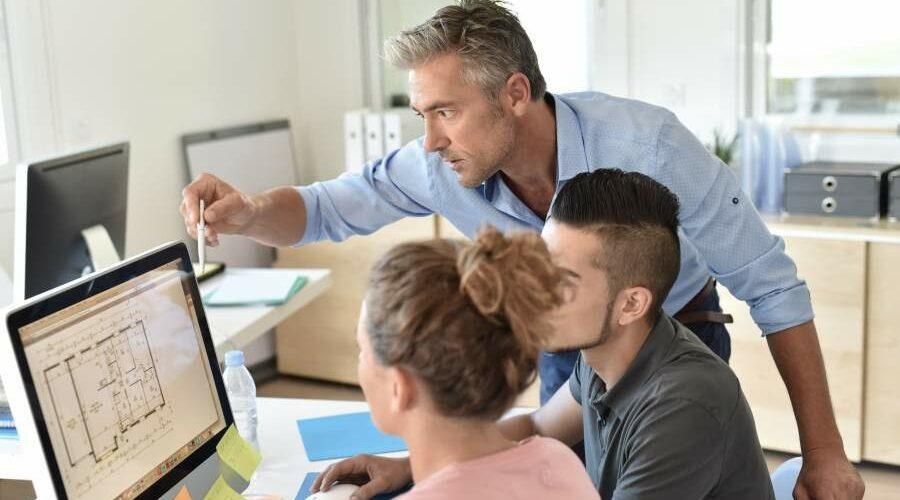Ausbilder in Architekturbüro erklärt etwas am Grundriss auf dem Bildschirm einer Auszubilden und einem Auszubildenden
