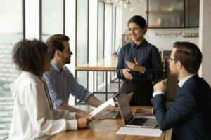Vier diverse Personen in Business-Meeting, Frau mit indischen Wurzeln lächelt und gestikuliert