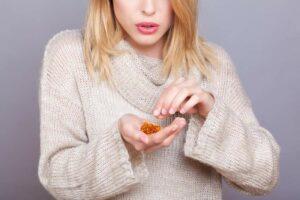 Junge Frau hält einige Nahrungsergänzungsmittel in Tablettenform in der rechten Hand und greift mit der linken Hand danach
