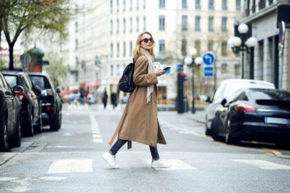 Junge Frau mit Sonnenbrille, Mantel, Schal und Rucksack überquert eine Straße über den Zebrastreifen
