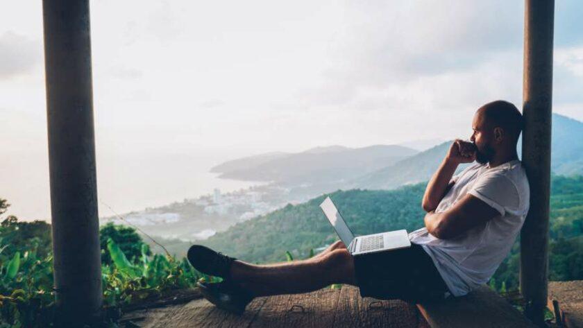 Junger Mann in Freizeitkleidung sitzt mit Laptop auf einer Veranda aus Holz und blickt nachdenklich in die Landschaft