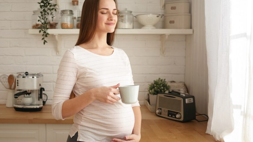 Schwangere Frau genießt eine Tasse Himbeerblaettertee zur Vorbereitung auf die Geburt