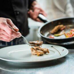 Mann in der Küche hält eine Pfanne neben einem Teller und richtet Gebratenes auf einem Teller an