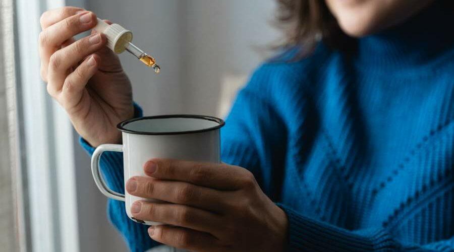 Frau lächelt und tropft mit einer Pipette CBD-Öl in eine Tasse
