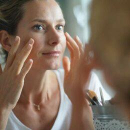 Close-up auf das Gesicht einer Frau, die sich im Spiegel betrachtet und die Haut ihrer Wangenknochen berührt