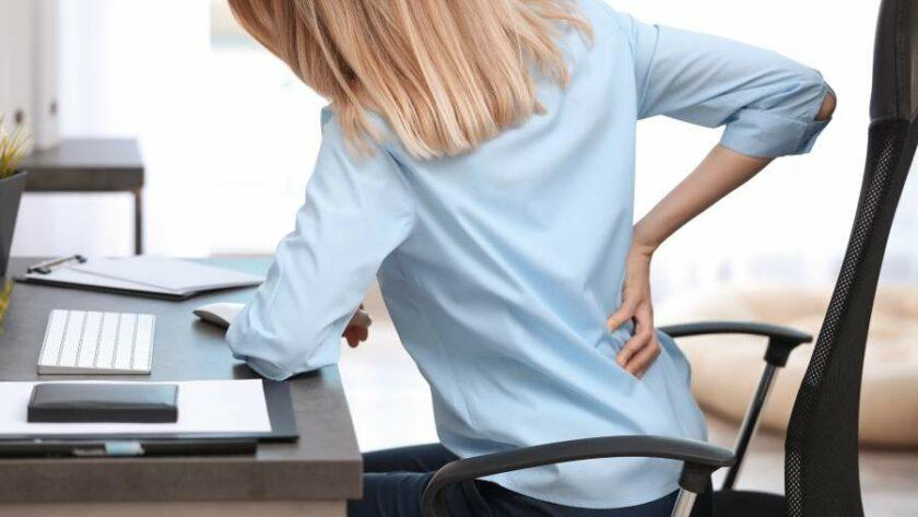 Junge Frau im Bürostuhl an Schreibtisch hält sich den Rücken in schmerzverzerrter Körperhaltung