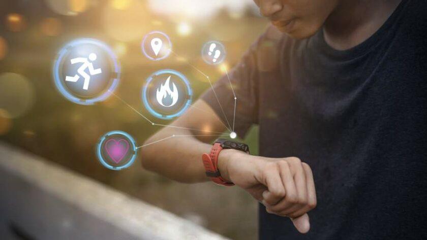Mann blickt auf das IoT-Wearable an seinem Handgelenk und kann Schritte und Gesundheitsdaten abfragen