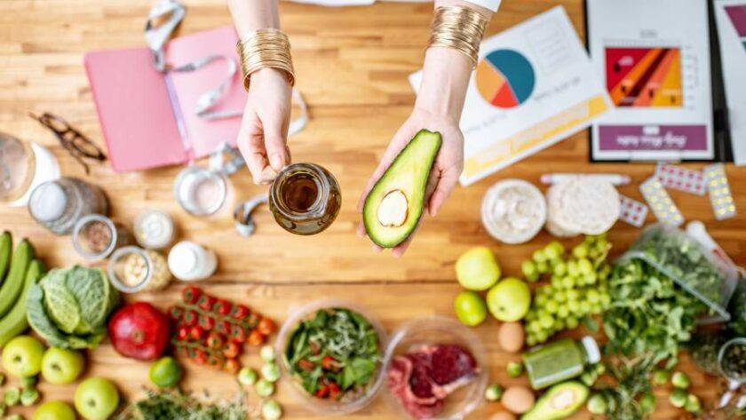 Vogelperspektive auf die Hände einer Ernährungsberaterin, die eine Glaskanne Öl und eine halbe Avocado über einem Tisch halten, darauf liegen Unterlagen, ein Maßband und verschiedene Lebensmittel