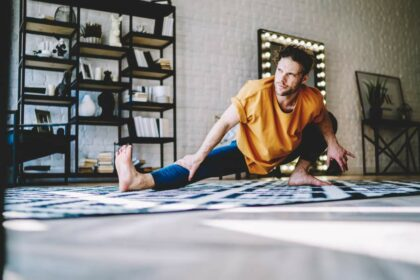 Junger sportlicher Mann macht Körpergewichtsübungen und Dehnübungen zu Hause