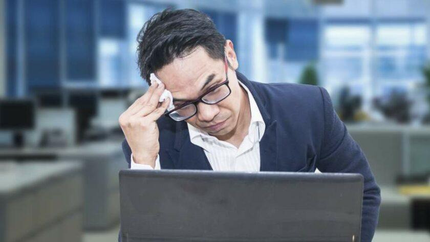 Geschäftsmann an Rechner in unbesetztem Großraumbüro blickt gestresst auf den Monitor und wischt sich den Schweiß von der Stirn