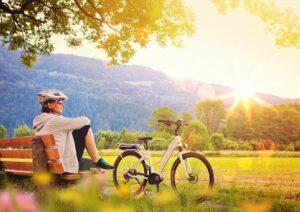 Frau mit Fahrradhelm und Sonnenbrille sitzt auf einer Bank in der Natur und in der Sonne, neben ihr steht ein Fahrrad