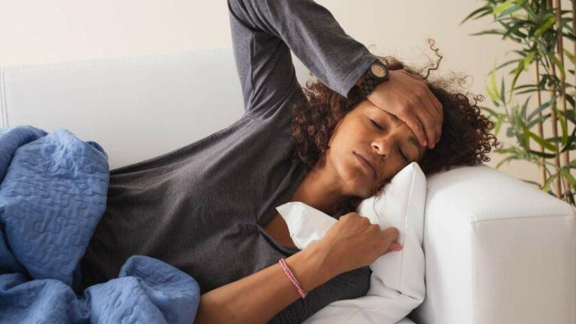 Junge Frau mit Krankheitssymptomen einer Erkältung oder Grippe liegt auf dem Sofa und hält die Hand an ihre Stirn
