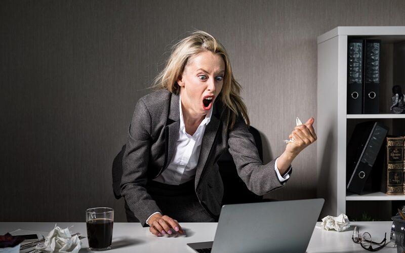 Wuetende Frau ist genervt von Werbung am Arbeitsplatz und schreit ihren Computer an