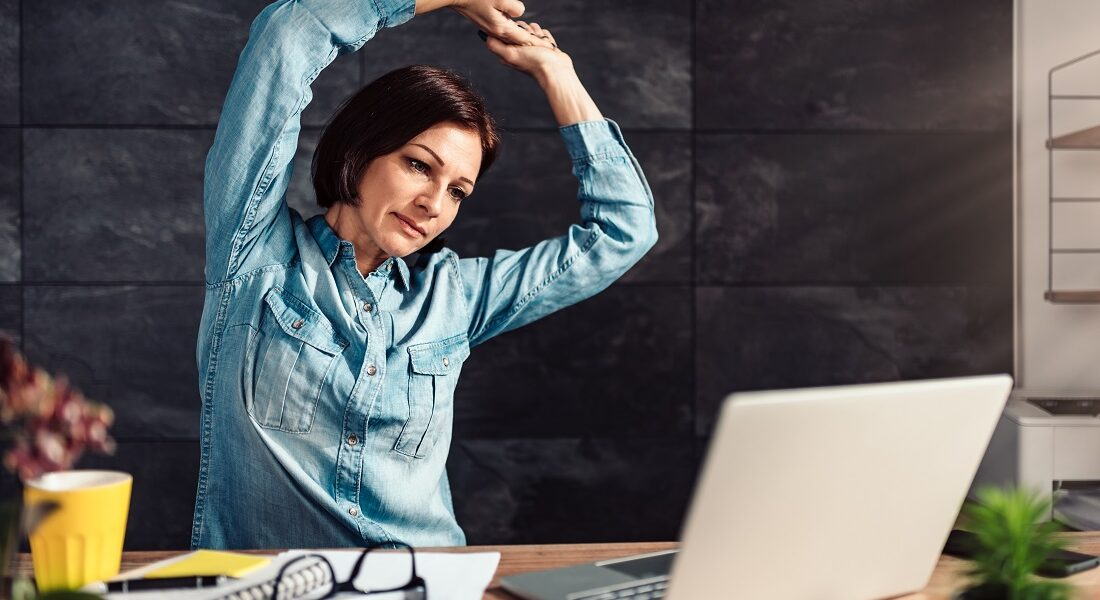 Frau macht Stretchinguebungen am Schreibtisch