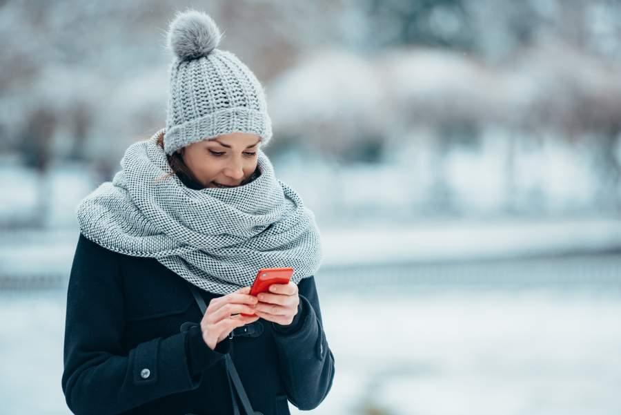 Junge Frau in Wintermütze, Schal und Mantel steht in verschneiter Landschaft und bedient ein Smartphone