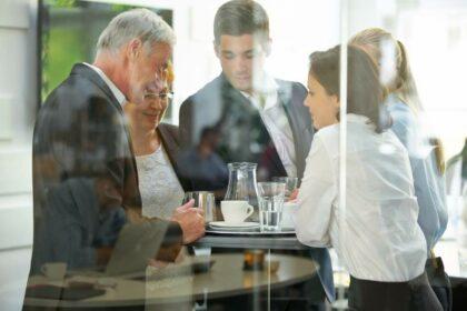 Diverse Mitarbeitende um einen Stehtisch in einer Cafeteria unterhalten sich